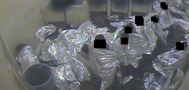 Una imagen tomada de un video sin fecha muestra a un grupo de hombres arropados con mantas isotérmicas en una celda.