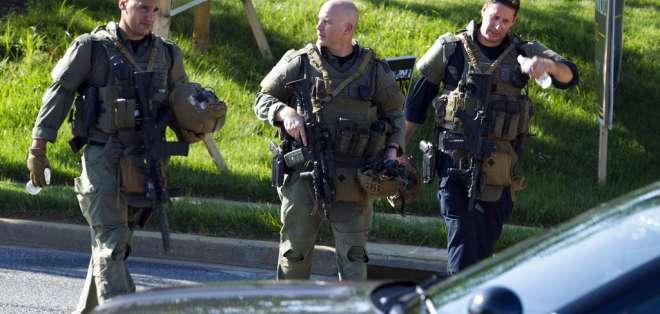 Tres agentes policiales caminan en el lugar donde varias personas fueron baleadas en el edificio de un periódico. Foto: AP