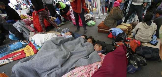 Migrantes venezolanos que no tienen con pasaporte aguardan en el puente internacional Rumichaca. Foto: AP