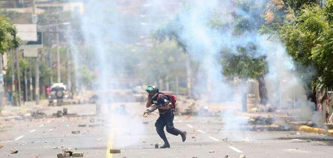 MANAGUA, Nicaragua.- Un policía se aleja de bombas caseras durante enfrentamientos con manifestantes. Foto: Archivo/ AP.