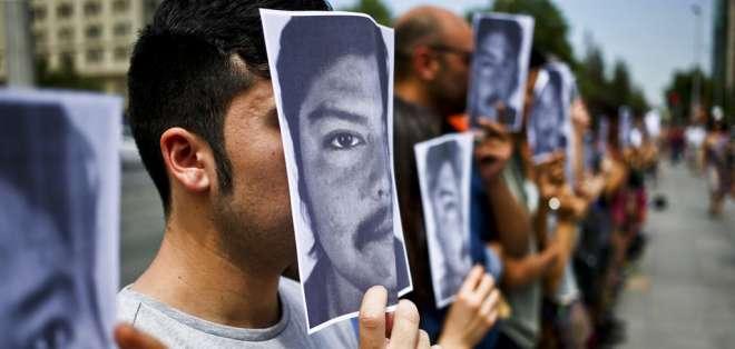 Estudiantes de la Universidad de Chile sostienen papeles con la imagen del mapuche Camilo Catrillanca. Foto: AP