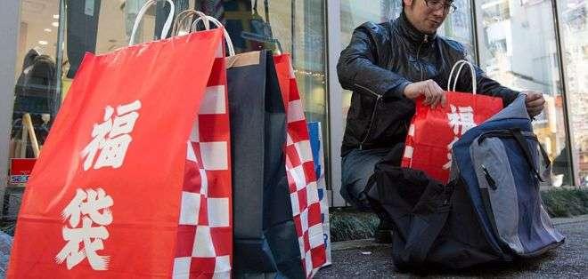 """Las palabras fukubukuro, o """"bolsa sorpresa"""", están escritas en caracteres japoneses en estas bolsas rojas de papel. Foto: GI"""