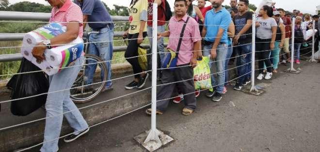 Venezolanos cruzan el Puente Simón Bolívar luego de comprar comida en Colombia. Foto: AFP