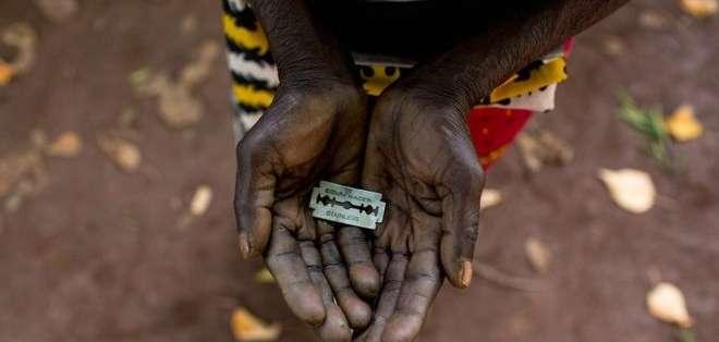 """Una mujer de Mombasa, Kenia, conocida como una """"mutiladora"""" , muestra la hojilla de afeitar que usa en los genitales de niñas."""