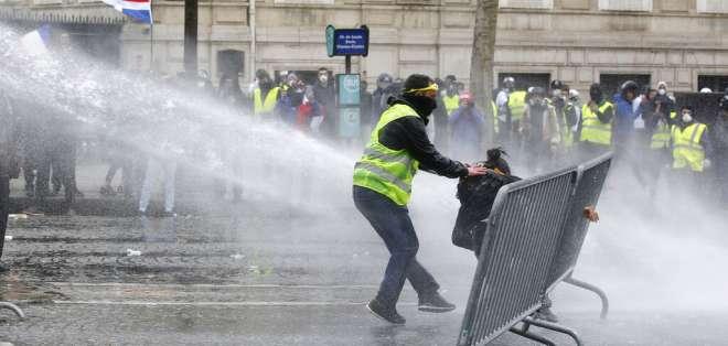 PARÍS, Francia.- Un manifestante de los chalecos amarillos rescata a otro mientras la policía utiliza cañones de agua. Foto: AP.