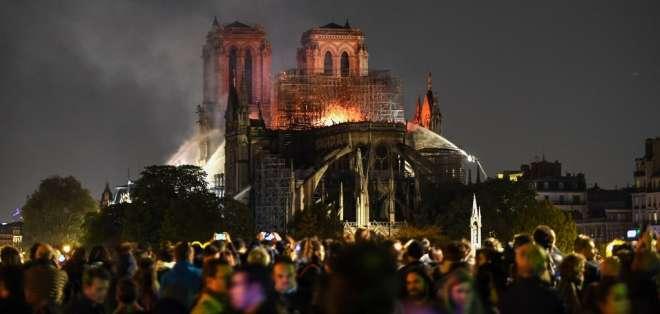 La multitud se aglutinaba a orillas del Sena, donde caían cenizas. Foto: AFP