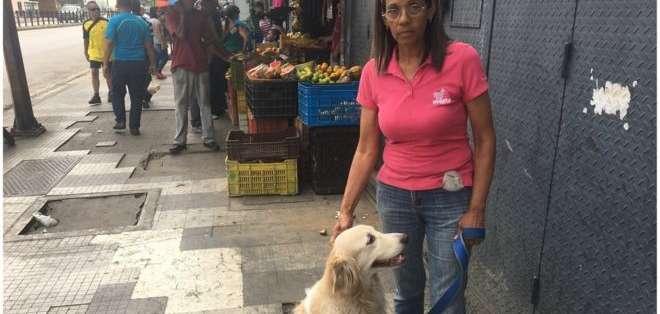 Gloria Barrero, con su perro, en un nuevo día de protestas en Caracas.