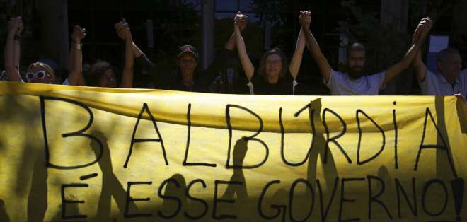 Estudiantes y maestros sostienen una pancarta durante una protesta en la Universidad de Brasilia a inicios de mayo. AP