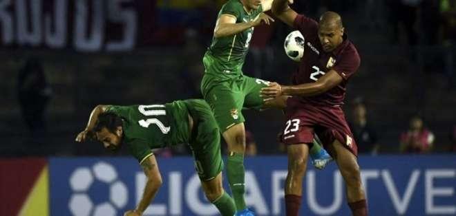 Jugador venezolano disputa el balón ante dos elementos bolivianos.