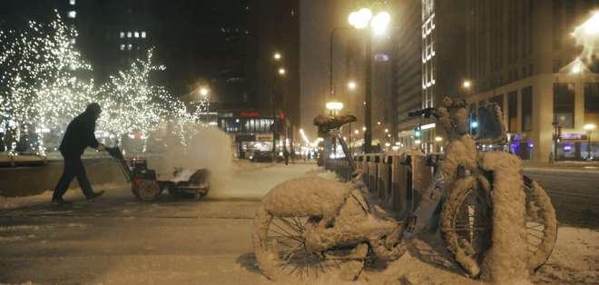 CHICAGO, EEUU.- Un empleado municipal retira nieve de una acera en la avenida North Michigan. Foto: AP