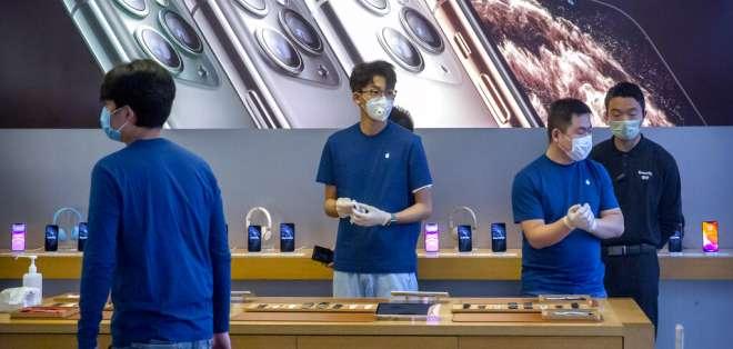 Empleados utilizan cubrebocas mientras trabajan en una tienda Apple en Beijing. Foto: AP Foto/Mark Schiefelbein