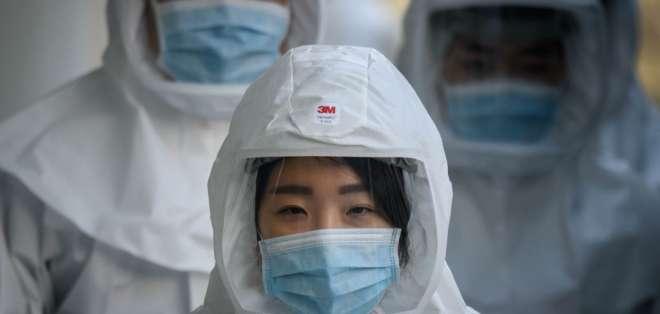 Médicos con trajes especiales, en una universidad de Corea del Sur. Foto: AFP