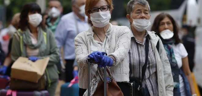 Personas caminan por las calles con mascarillas de protección por coronavirus. Foto: EFE - Referencial