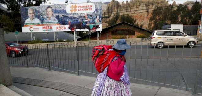 Una mujer camina cerca de un cartel del candidato presidencial Carlos Mesa. Foto: AP