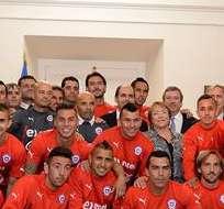 SANTIAGO DE CHILE.- La mandataria Michelle Bachelet mientras posa con los jugadores de la selección nacional de fútbol. Foto: EFE.