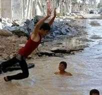 SIRIA.- Niños chapoteaban con alegría en un charco de agua formado en una calle destruida por los bombardeos. Foto: Agencia