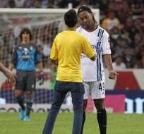 Ronaldinho firmó el autógrafo y el hincha fue sacado del campo por la seguridad. Foto: EFE.