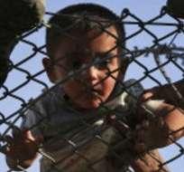 Miles de familias han traspasado las fronteras hacia Turquía. En la foto, un bebé es pasado por la malla de alambre en Sanliurfa, en el sureste de Turquía.