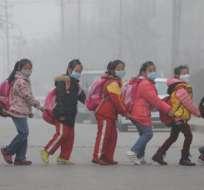 JINAN, China.- Estudiante chinos van a la escuela con mascarillas para protegerse de la contaminación ambiental. Foto AFP