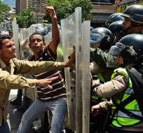 Venezolanos se enfrentan con policías durante protestas por la falta de comida y medicinas en Caracas. Foto: AFP