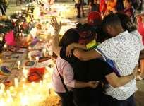 Personas se abrazan cerca de un memorial en recuerdo de los fallecidos por el ataque en Orlando. Foto: AFP