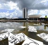 Manifestantes colocan pancartas que representan a las ratas en una fuente frente al Congreso Nacional en Brasilia durante una protesta contra la corrupción y en apoyo de la operación anticorrupción Lava Jato que investiga el escándalo de sobornos de Petrobras, el pasado 4 de diciembre de 2016. Foto: AFP