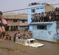 Una mujer es sacada de la inundación mediante una tirolesa improvisada en Lima. Foto: AP