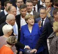 """La canciller de Alemania, Angela Merkel (centro), gesticula mientras una legisladora levanta un cartel con la palabra """"No"""" durante una sesión del parlamento alemán, Bundestag, en el edificio del Reichstag, sobre los matrimonios homosexuales. Foto: AP"""