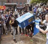 Un joven lanza una caja expendedora de periódicos contra manifestantes el sábado 12 de agosto del 2017 durante una manifestación de nacionalistas blancos contra un grupo de oposición. Foto: AP