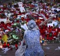 BARCELONA, España.- Mujer se detiene frente a varias velas y flores colocadas en honor a los fallecidos en los atentados. Foto: AP.
