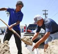 Leo Sermiento, a la izquierda, y Emilio Gutierrez, a la derecha, llenan bolsas de arena en preparación de una tormenta el miércoles 23 de agosto de 2017, en South Padre Island, Texas. Foto: AP