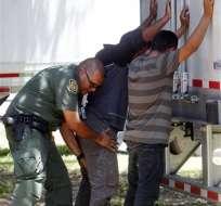 En esta fotografía del domingo 13 de agosto de 2017, un agente de la Patrulla Fronteriza registra a unos hombres que fueron encontrados con un grupo de inmigrantes encerrados en el remolque de un camión de carga estacionado en una gasolinera en Edinburg, Texas, a unos 30 kilómetros (20 millas) de la frontera con México. Foto: AP
