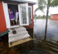 En esta imagen del 11 de septiembre de 2017, Quintana y Liz Perez miran a la inundación ante su casa, tras el paso del huracán Irma por Immokalee, Florida, una de las localidades más pobres del estado. Foto: AP