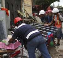 En esta imagen, tomada el 22 de septiembre de 2017, Héctor Rodarte (derecha) ayuda a recuperar artículos personales de la casa de un vecino destrozada por un sismo de magnitud 7,1, en Jojutla, en el estado de Morelos, México. Foto: AP