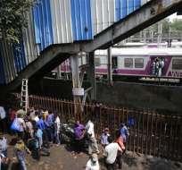 Peatones de pie bajo un puente peatonal donde hubo una estampida en la estación de tren de Elphinstone, en Mumbai, India, el viernes 29 de septiembre de 2017. Foto: AP