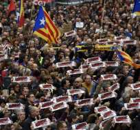 """La gente sostiene pancartas que dicen """"presos políticos libres"""" y banderas catalanas a favor de la independencia. Foto: AFP"""
