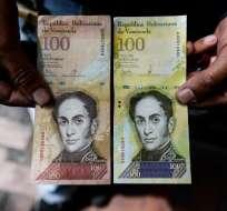 Un hombre sostiene el nuevo billete de cien mil Bolivar-note que lo compara con el billete de cien, para mostrar el parecido entre ambos, en Caracas el 9 de noviembre de 2017. Foto: AFP