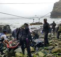 Olas que alcanzan los restos del autobús volcado dificultaban las tareas de rescate. Foto: AP