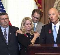 Padres de las víctimas junto a gobernador de Florida, Rick Scot. Foto: AP.