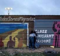 Un niño mira a través de la cerca entre EE.UU. y México, acompañado por su madre. Foto: AFP