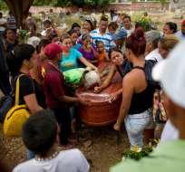 VALENCIA, Venezuela.- Familiares entierran a las víctimas del incendio en cárcel de Carabobo. Foto: AP.