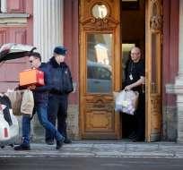 SAN PETERSBURGO, Rusia.- Unos hombres sacan unas cajas del consulado. Foto: AP.