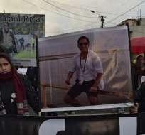 QUITO, Ecuador.- Familiares y amigos de Javier Ortega sostienen una pancarta con su fotografía. Foto: AFP.