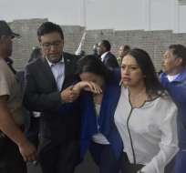 Asambleísta Gabriela Rivadeneira camina acompañada por compañeros de bancada tras incidente. Foto: AFP.