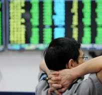Un guardia de seguridad se sienta frente a las pantallas que muestran las cifras del mercado bursátil en una empresa de valores.