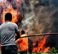 24 de julio: bomberos y voluntarios intentan extinguir las llamas de un incendio en la aldea griega de Kineta.
