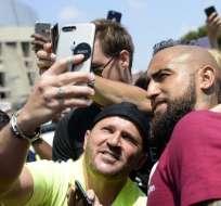 BARCELONA, España.- El mediocampista Arturo Vidal posa junto a fanáticos del F.C. Barcelona tras firmar su contrato. Foto: AFP