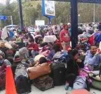 Migrantes venezolanos sentados en los exteriores de la oficina de migración ecuatoriana de Tulcán. Foto: Cortesía.