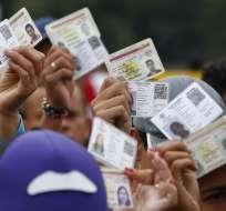 Ciudadanos venezolanos alzan sus cédulas de identidad para ser inspeccionados en Colombia. Foto: AP