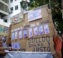 Enfermeros sostienen un letreros con billetes venezolanos falsos que representan los salarios bajos por inflación. Foto: AP